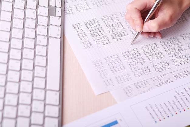 Image d'une main de femme écrivant sur du papier avec des nombres