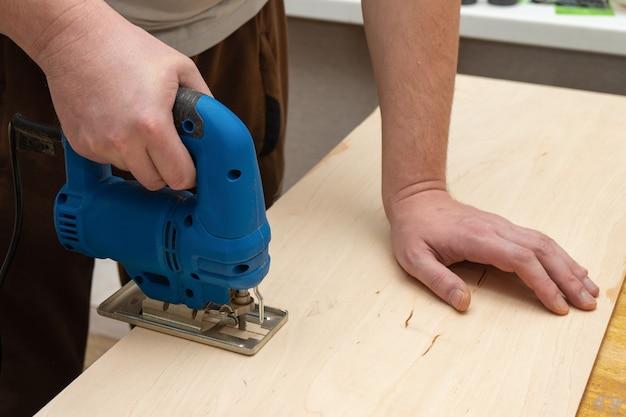 Image d'une main d'homme à l'aide d'une scie sauteuse électrique. fermer le processus de découpe de planche de bois.