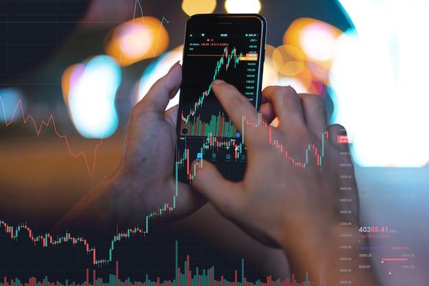 Image de la main d'un homme utilisant son téléphone pour vérifier la bourse