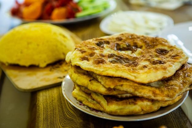 Image avec les mains d'une dame cuisinant des tartes frites roumaines traditionnelles avec du fromage