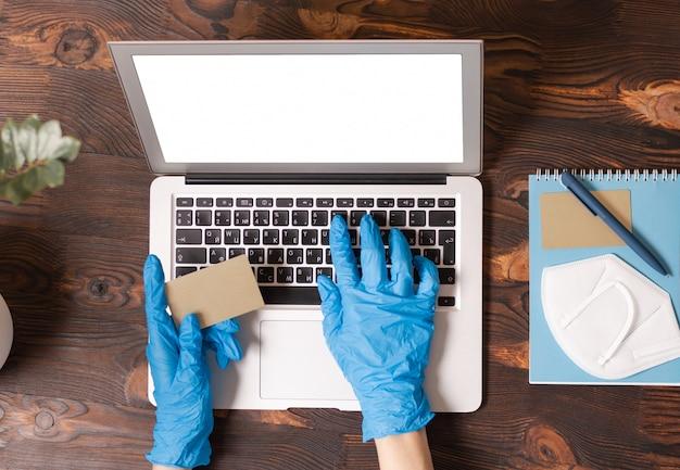 Image de mains dans des gants médicaux tenant une carte de crédit et en tapant sur un ordinateur portable. vue de dessus.