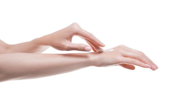 Image de mains féminines appliquant de la crème sur la peau. concept médical de soins de la peau et des mains sains. technique mixte
