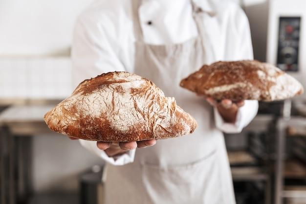 Image de mâle boulanger en uniforme blanc debout à la boulangerie, et tenant du pain