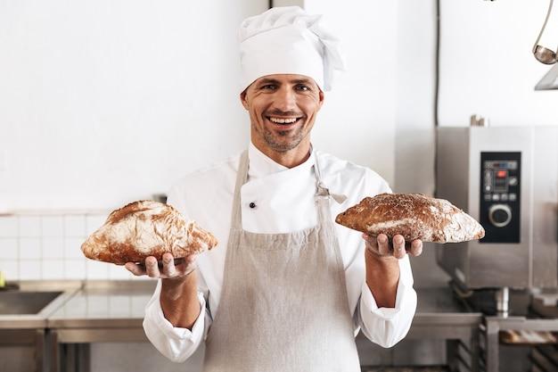 Image de mâle caucasien boulanger en uniforme blanc debout à la boulangerie, et tenant du pain