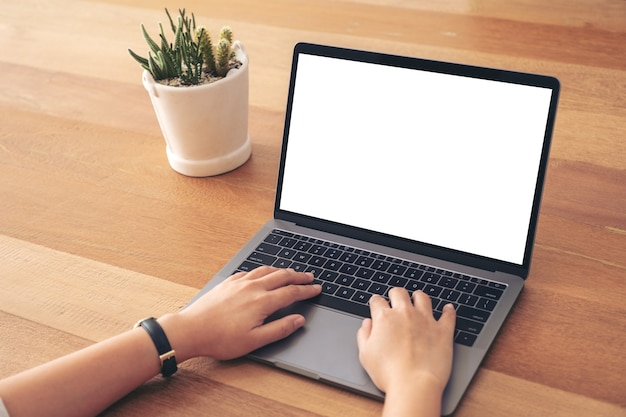 Image de maquette d'une femme à l'aide et en tapant sur un ordinateur portable avec écran blanc vierge sur table en bois