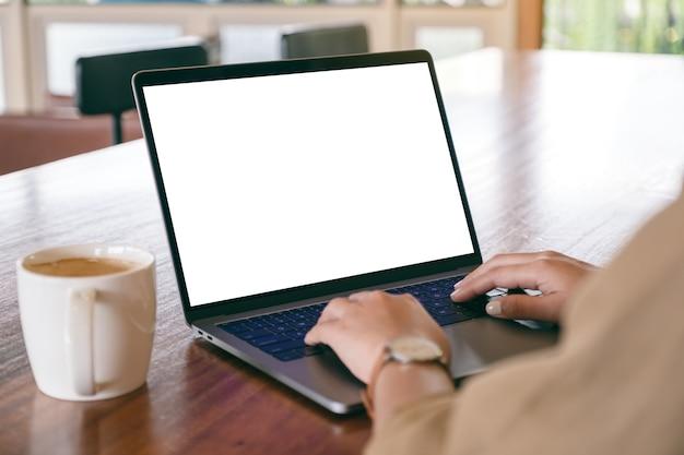 Image de maquette d'une femme à l'aide et en tapant sur un ordinateur portable avec écran blanc vierge et tasse à café sur table en bois