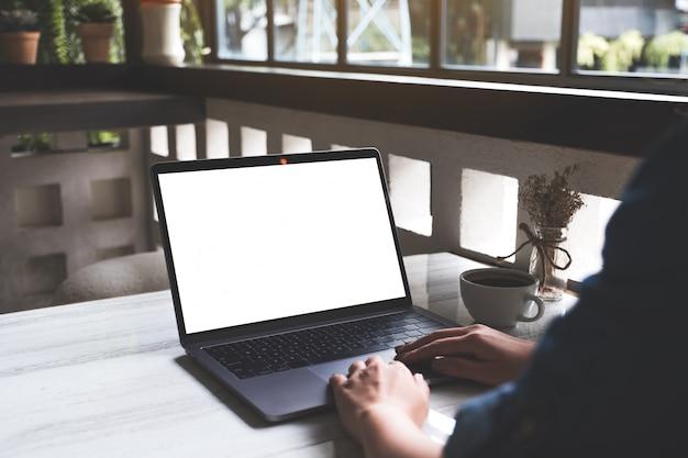 Image maquette d'une femme à l'aide et en tapant sur un ordinateur portable avec écran blanc vierge et tasse de café sur la table dans un café moderne