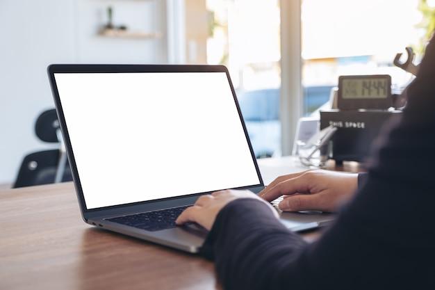 Image de maquette d'une femme à l'aide et en tapant sur un ordinateur portable avec un écran de bureau blanc vierge