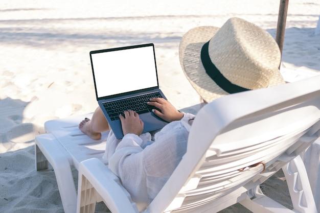 Image de maquette d'une femme à l'aide et en tapant sur un ordinateur portable avec écran de bureau vide tout en fixant sur une chaise de plage sur la plage