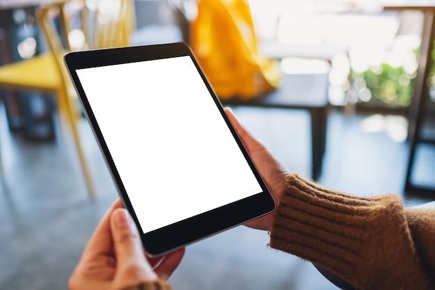 Image maquette d'une femme assise et tenant un tablet pc noir avec un écran de bureau blanc vierge