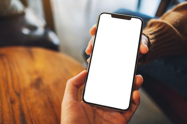 Image maquette d'une femme tenant et montrant un téléphone portable blanc avec un écran de bureau noir vierge à quelqu'un