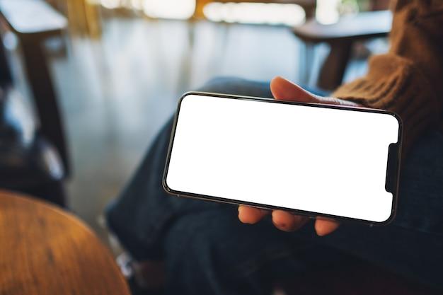 Image maquette d'une femme tenant et montrant un téléphone portable noir avec écran vide dans un café