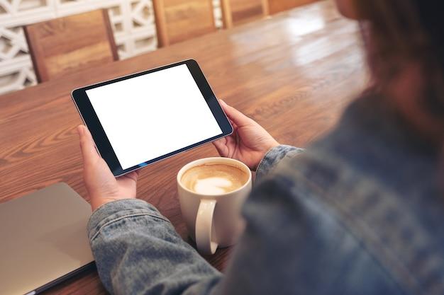 Image de maquette d'une femme tenant un tablet pc noir avec écran blanc vide horizontalement avec tasse de café et ordinateur portable sur table en bois