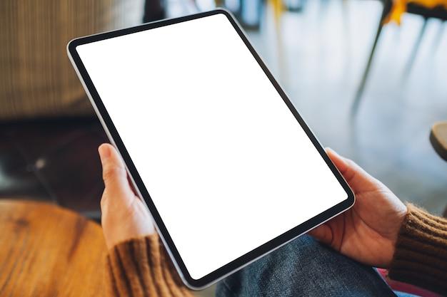 Image maquette d'une femme tenant un tablet pc noir avec un écran blanc vierge sur une table en bois
