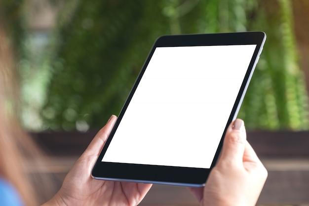Image maquette de femme tenant un tablet pc noir avec écran de bureau blanc blanc