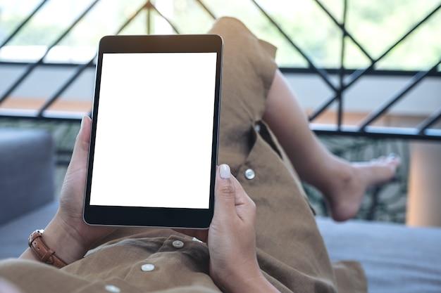 Image de maquette d'une femme tenant un tablet pc noir avec écran de bureau blanc vierge tout en fixant dans la salle de séjour avec une sensation de détente