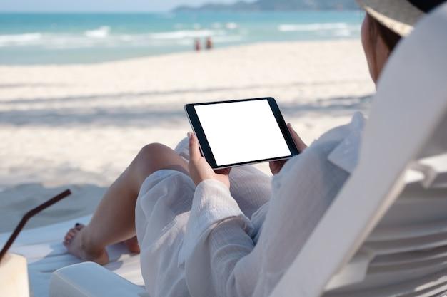 Image de maquette d'une femme tenant un tablet pc noir avec écran de bureau vide tout en fixant sur une chaise de plage sur la plage
