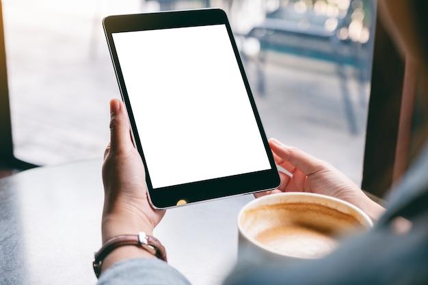 Image de maquette d'une femme tenant une tablette noire avec un écran blanc blanc et une tasse de café sur la table