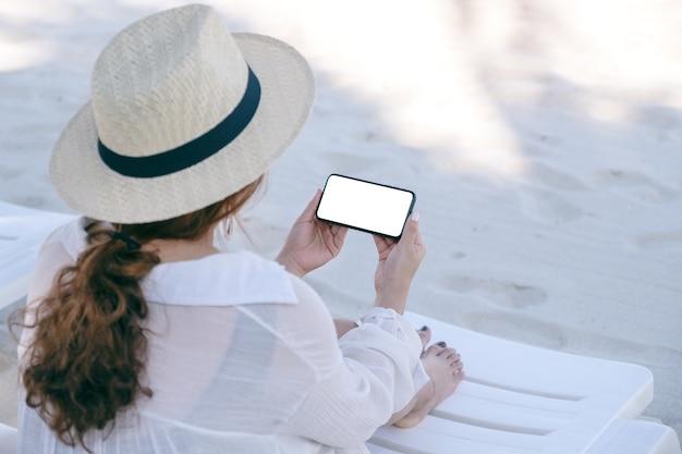 Image de maquette d'une femme tenant un téléphone mobile blanc avec écran de bureau vide tout en fixant sur une chaise de plage sur la plage