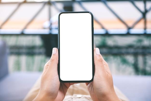 Image de maquette d'une femme tenant un téléphone mobile noir avec écran de bureau blanc vierge tout en fixant dans le salon avec une sensation de détente