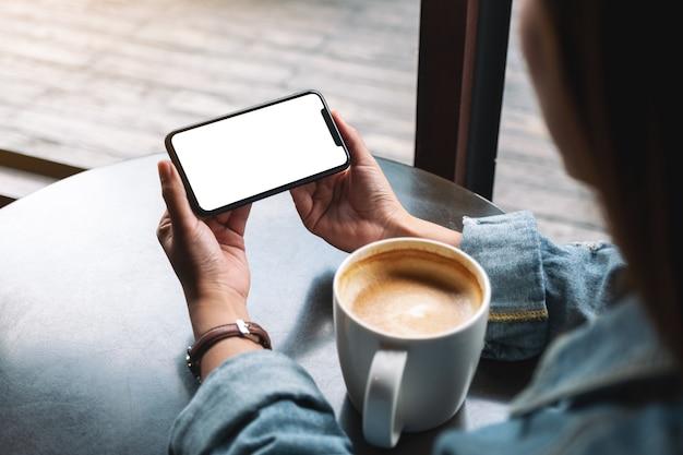 Image maquette d'une femme tenant un téléphone portable noir avec écran blanc avec une tasse de café sur une table en bois