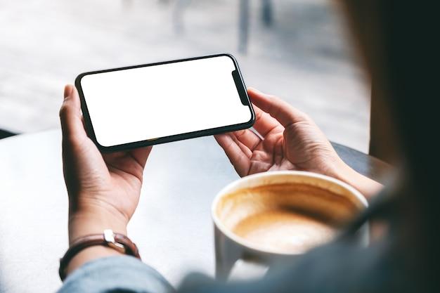 Image maquette d'une femme tenant un téléphone portable noir avec écran blanc avec une tasse de café sur la table