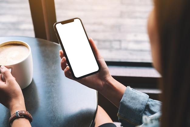 Image de maquette d'une femme tenant un téléphone portable noir avec un écran vide tout en buvant du café
