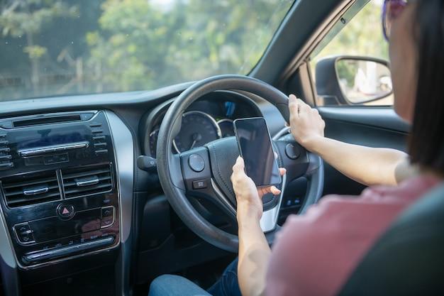 Image maquette d'une femme tenant et utilisant un téléphone portable avec écran vide pendant qu'elle conduit une voiture, pour gps, photo de modes de vie en voiture, intérieur, vue de face. avec la main de femme tenant le téléphone.