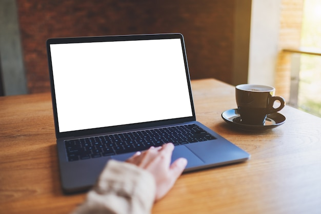 Image de maquette d'une femme utilisant et touchant le pavé tactile d'un ordinateur portable avec un écran de bureau blanc vierge avec une tasse de café sur une table en bois