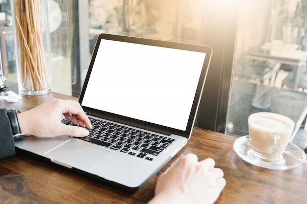 Image maquette de l'homme d'affaires en utilisant et en tapant sur ordinateur portable avec écran blanc vierge