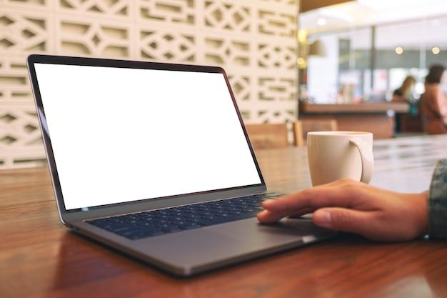Image de maquette d'une main de femme à l'aide et en touchant le pavé tactile de l'ordinateur portable avec un écran de bureau blanc vierge avec une tasse de café sur une table en bois