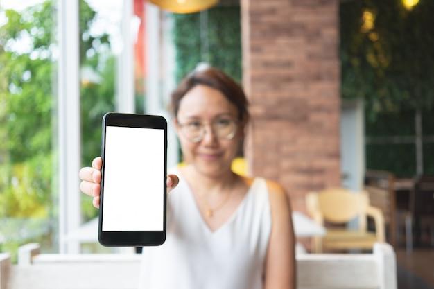 Image de la maquette de la main de femme tenant écran blanc isolé de smartphones mobiles