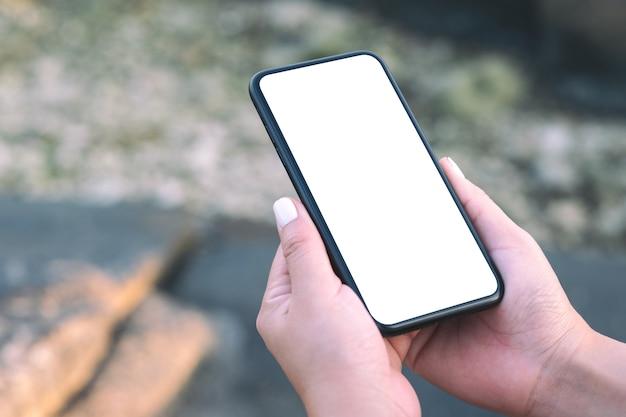 Image de maquette de la main de la femme tenant un téléphone mobile noir avec écran de bureau vide par la plage et la mer