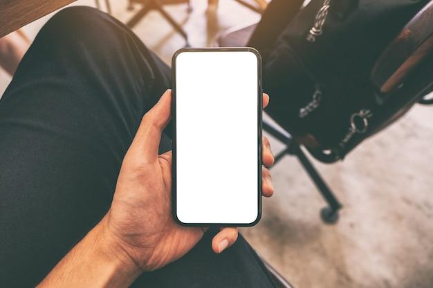 Image de maquette de la main d'un homme tenant un téléphone mobile noir avec écran blanc avec une tasse de café sur la table au café