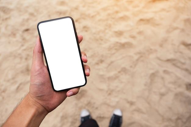 Image maquette de la main d'un homme tenant un téléphone portable noir avec un écran de bureau vierge en se tenant debout sur la plage