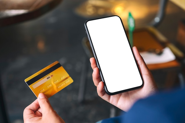 Image de maquette d'une main tenant une carte de crédit et d'un téléphone portable noir avec un écran de bureau vierge