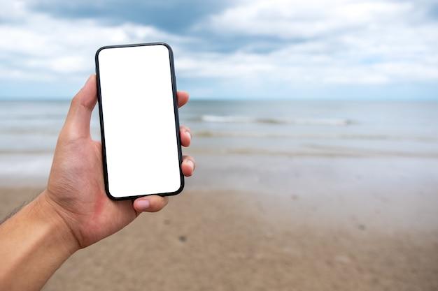 Image de maquette d'une main tenant et montrant un téléphone portable noir avec un écran de bureau vierge sur la plage