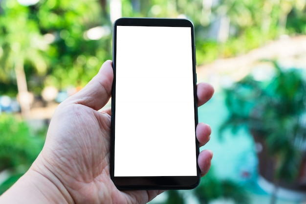 Image de la maquette de la main tenant le téléphone portable avec écran blanc