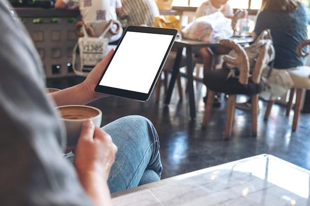 Image de maquette des mains de femme tenant un tablet pc noir avec écran blanc