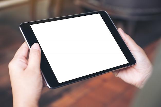 Image maquette de mains de femme tenant un tablet pc noir avec écran de bureau vide au café