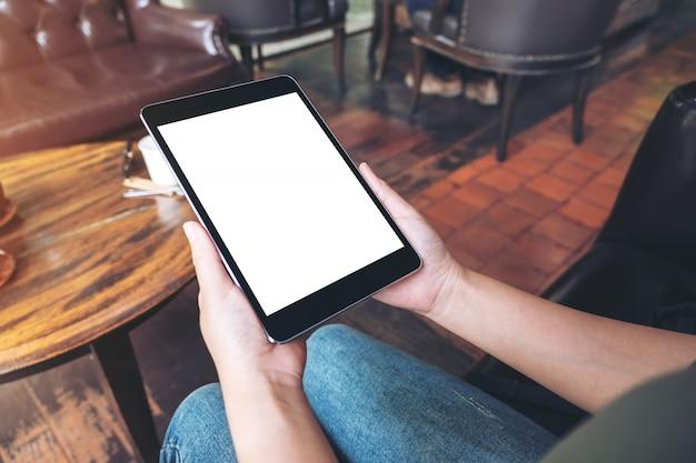 Image maquette de mains de femme tenant un tablet pc noir avec un écran de bureau vide tout en étant assis dans un café