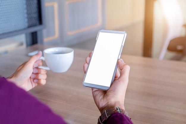 Image de la maquette des mains de l'homme sur un téléphone portable blanc avec la technologie d'écran blanc.