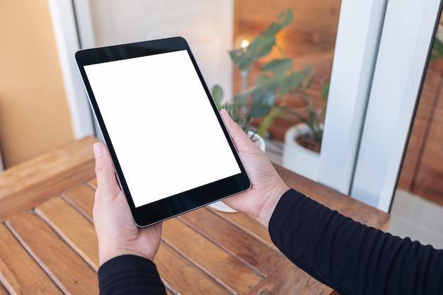 Image de maquette de mains tenant et regardant tablet pc avec écran blanc vierge