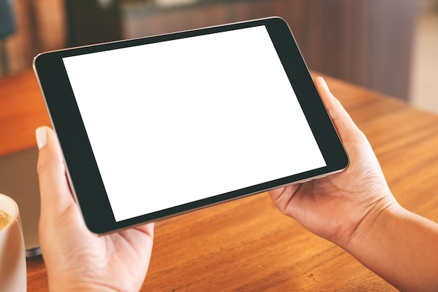 Image de maquette de mains tenant un tablet pc noir avec écran blanc vierge avec ordinateur portable et tasse à café sur table en bois