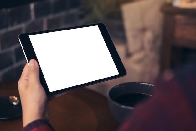 Image de la maquette des mains tenant une tablette noire avec écran blanc et tasse à café