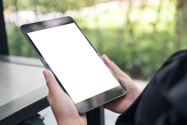Image de la maquette des mains tenant une tablette noire avec un écran de bureau blanc sur la table