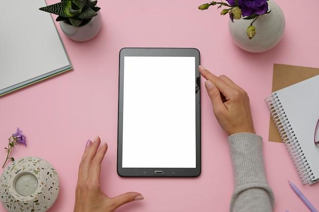 Image de la maquette des mains tenant une tablette pc sur le bureau rose.