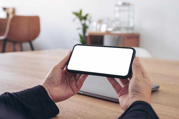 Image de maquette de mains tenant un téléphone mobile noir avec écran blanc vierge