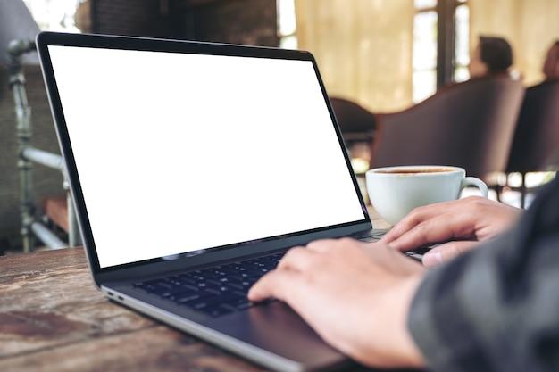 Image de maquette de mains en utilisant et en tapant sur un ordinateur portable avec un écran de bureau blanc vierge