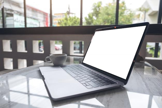 Image maquette d'ordinateur portable avec écran de bureau blanc vierge et tasse de café sur une table en bois au café